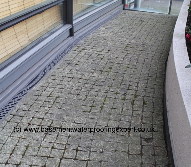 Permeable block paving and aco drain formed on podium deck, against external wall of apartment building.